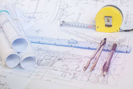 Tool designer in the construction industry. Ruler, compass and pencil lying on the engineering drawings.