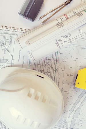 Accessories construction engineer. White safety helmet lies on the drawings. Coils projects near the black stamp on the documents. Vertical frame flat lay.