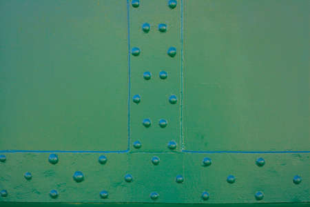Metal surface connected by rivets. Metal painted green. The element of the surface area of a railroad car Stock Photo