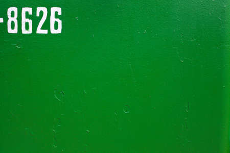 White numbers on a green background. Painted metal surface. Metal painted green. Iron plates welded together.