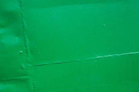 The green background. Painted metal surface. The surface of the train as a background element. Metal painted green. Iron plates welded together. A diagonal position.