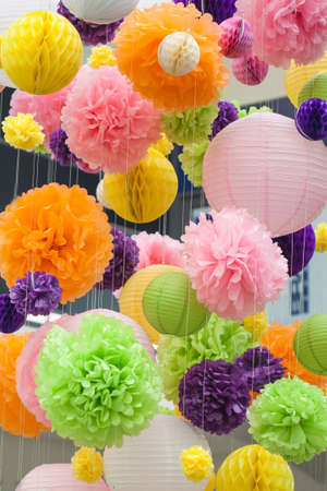 Bright decorations of paper colored POM-poms. POM-poms made of paper hanging from the ceiling. Background of colored spots.