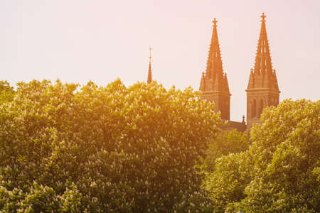 The towers of the Cathedral peeking out from behind the trees. Spires of the building in the Gothic style are buried in greenery. The bright sun shines on the towers of a medieval building in Prague. Stock fotó