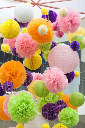 Element of decoration made of paper in the interior. Bright decorations of paper colored POM-poms. POM-poms made of paper hanging from the ceiling. Background of colored spots.
