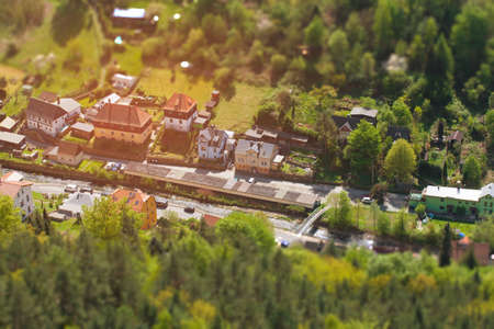 House near a stream in a forest with effect of tilt shift. The building of the suburbs near the river in miniature. Selective focus on the countryside from the height of the helicopter.