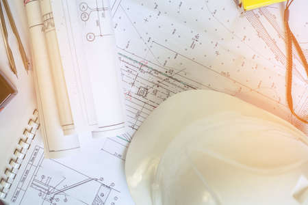 The sun illuminates the table with documents. A metal compass lies on the drawings. Accessories construction engineer. White safety helmet lies on the drawings. Coils projects on the documents.