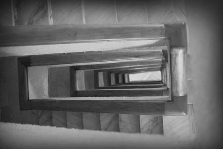 Stair in black and white. The lonely spiral stairs in the hotel to curl deep down. Perspective of stair railings in the form of an abstract background. The tunnel from the stairwells goes deep.