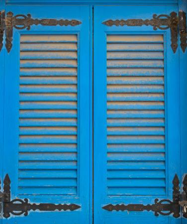 Ancien store pare-soleil à double aile bleu dans un format vertical