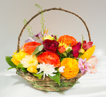Bouquet of flowers in a basket on a gray background 写真素材