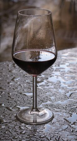 Glass of red wine on a table with drops of rain