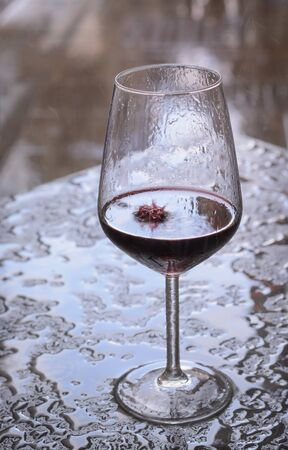 Glass of red wine with rain drops