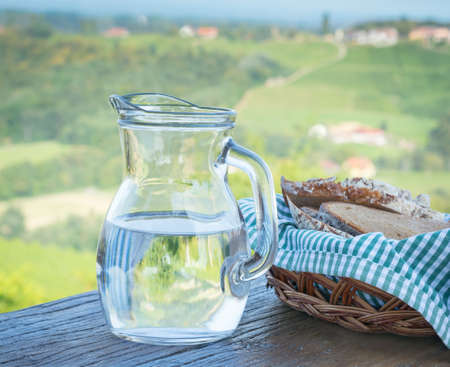 Glass jug with water and bread on a blurred background