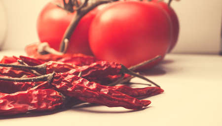 Dried red chili peppers on a tomato background Stock Photo
