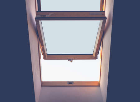 the window in the middle in the ceiling of the room is ajar