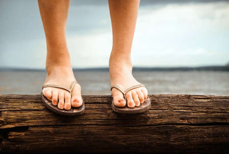 Feet of a girl standing on a log that lies on the sand by the water