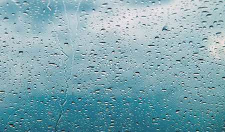 Drops of water flow down the glass in the rain