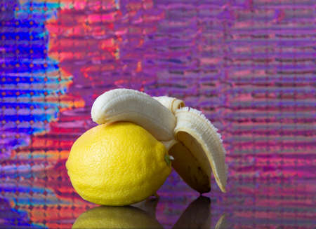fruits on the mirror bananas, cherry, lemon with a colored background Imagens