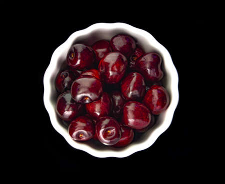 cherry on a white plate on a black background