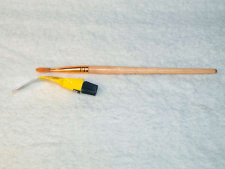 Paint brush and tube of yellow paint on a white background