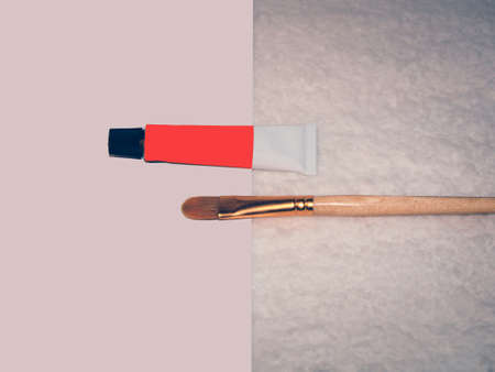 Brush for painting and a tube of orange paint on a white background Standard-Bild