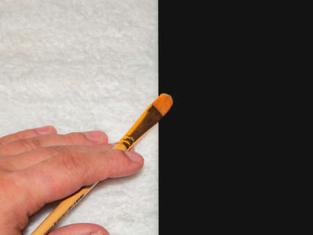 Brush for painting in hand on a black and white background Foto de archivo
