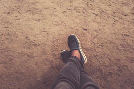 Male legs in sneakers on the background of sand at dusk