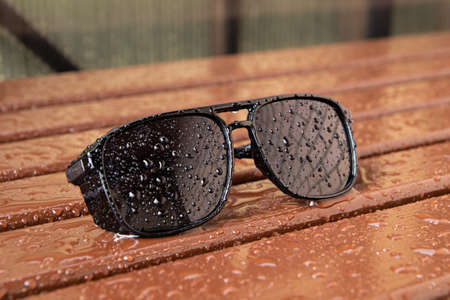 Sunglasses in the rain on old wooden background. Raindrops flow down women's sunglasses
