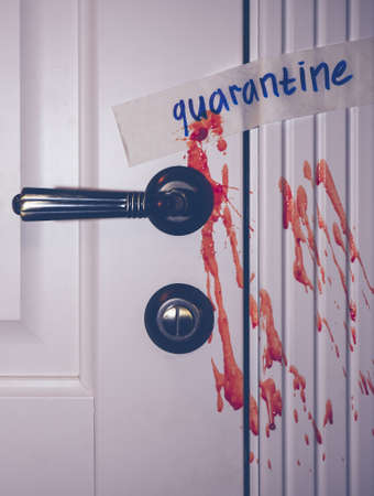 quarantine inscription on a wooden door. Blood splatters on the door. metal door handle