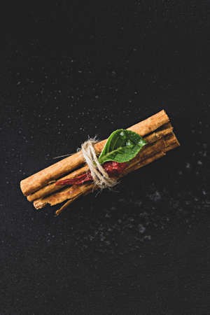 A bunch of cinnamon sticks on a black