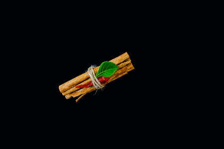 bunch of cinnamon sticks on black background with red dried pepper and green leaf Imagens