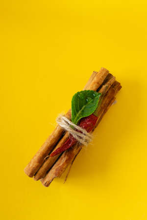 a bunch of cinnamon sticks on a colored background with red dried pepper and green leaf