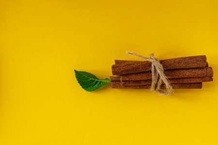 bunch of cinnamon sticks on a colored background with a green leaf. Imagens