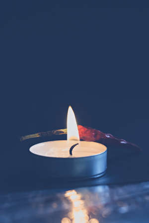 Burning non-scented candle with red pepper in the dark