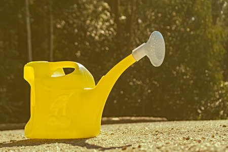 There is a yellow watering can with a white shower in the yard