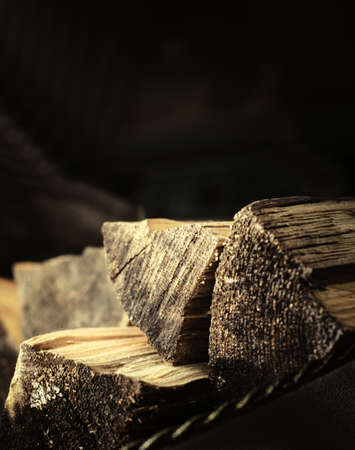 Chipped firewood lie near the fireplace on a dark background Imagens