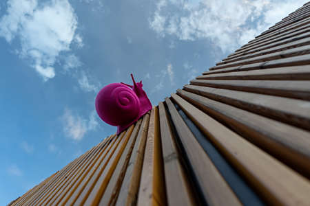 Large pink plastic snail crawling on wooden planks against the sky