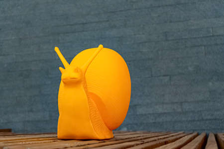Large yellow plastic snail crawling on wooden planks Imagens