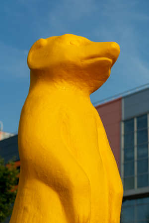 A figure of a meerkat made of colored plastic stands in the park on the grass Imagens