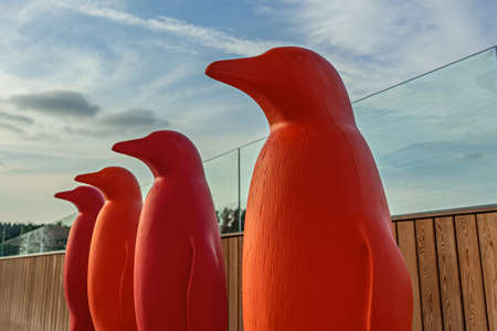 four red plastic penguins in the park Imagens