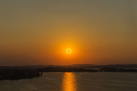 The sun is low over the horizon during sunset over the lake Imagens