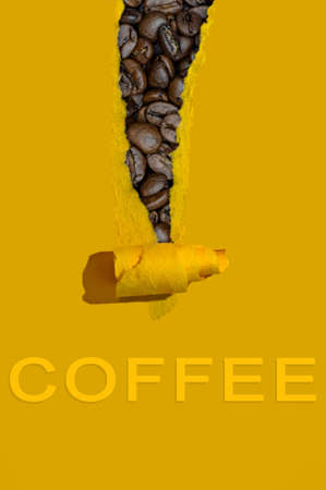 Torn sheet of yellow paper with coffee beans peeping out and lettering
