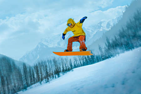 Snowboarder jumps through the air against the background of forest and mountains in snow caps