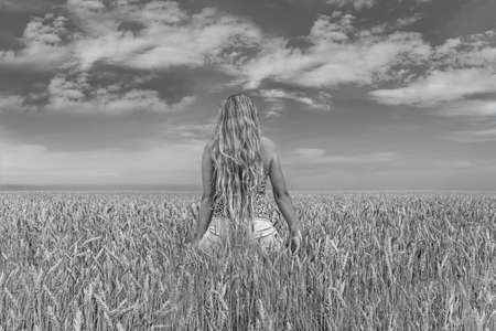 black and white toned portrait of a young girl in a summer field from the back