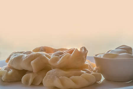 dumplings with sour cream on a plate on a wooden background-top view Imagens