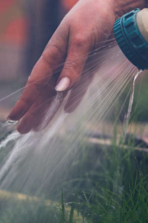 Girl watering her hand under a garden tap over green grass