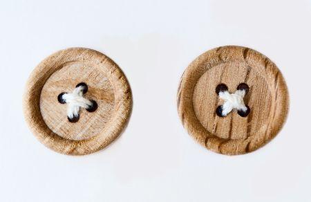 白の背景に分離された 2 つの木製縫ったボタン