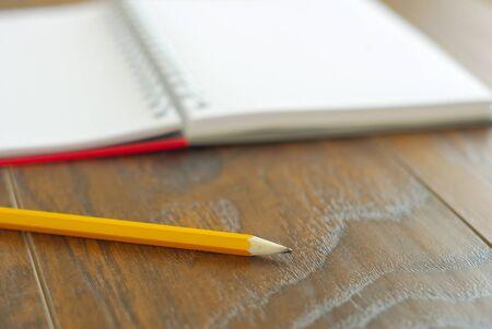 Yellow pencil memo notes organizer. Open notebook memories reminder. Education stationary closeup.