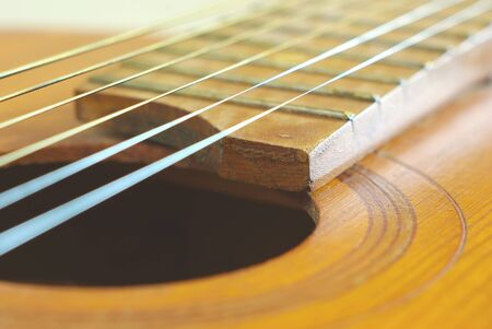 Old wooden string guitar closeup. Vintage acoustic music background. Musical classical instrument. Stock Photo