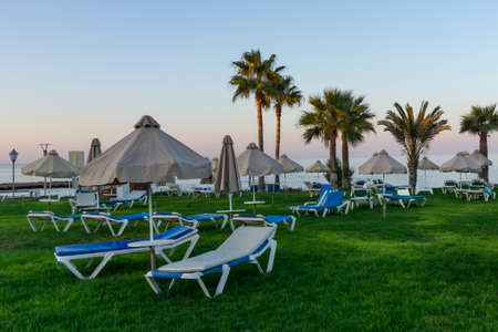 Cyprus.Beach with  umbrellas and sunbeds  without people.Beautiful view on the Sunset. 免版税图像