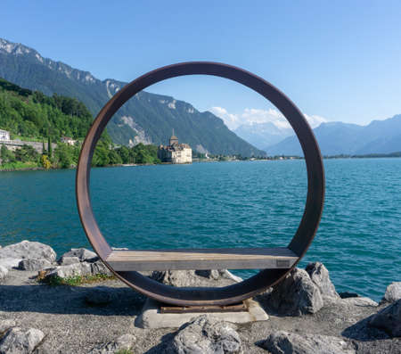 A large metal circle with a simple wooden bench. Lake view with an old castle and hills in the distance